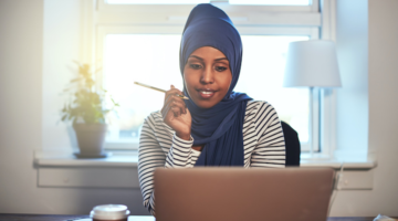 Woman in hijab sits in front of her laptop with pencil in hand