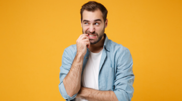 Man stands against a bright yellow background, biting his finger in a look of confusion.