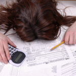 Woman is face down, head in a pile of tax documents with a calculator in one hand and a pencil in the other.