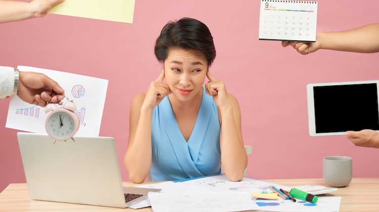 Woman at desk with laptop and papers blocking ears as a bunch of hands compete for her attention