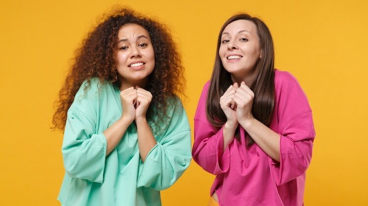 Two women against mustard backdrop, one in green shirt one in pink, hold hands together in pleading motion.