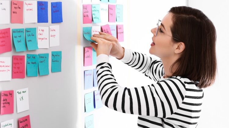 Woman in black-and-white striped shirt peels a teal sticky note from a sea of sticky notes in white, teal, and red, off a whiteboard.