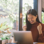Young Asian woman sitting in front of laptop pumps both fists while smiling.
